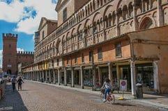 Vista di vecchia costruzione con la gente ed i negozi, vicino alla cattedrale di Ferrara Immagine Stock