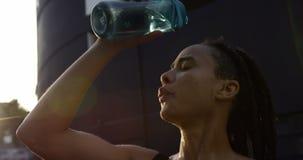 Vista dianteira da água de derramamento da mulher afro-americano nova em sua cabeça na cidade 4k vídeos de arquivo