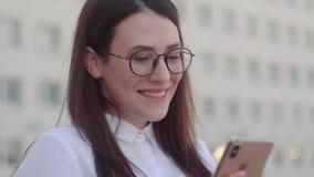 Vista dianteira da camisa branca vestindo de sorriso da mulher de negócio usando um telefone esperto em uma rua da cidade Tiro do vídeos de arquivo