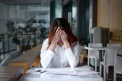 Vista dianteira da cara asiática nova frustrante forçada da coberta da mulher de negócio com mãos na mesa no escritório foto de stock