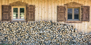 Vista dianteira da casa de madeira do chalé com pilha de madeira Foto de Stock