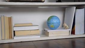 Vista dianteira da prateleira com livros e um globo vídeos de arquivo