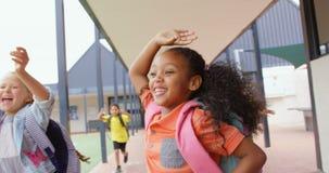 Vista dianteira de alunos da misturado-ra?a com os schoolbags que correm no corredor na escola 4k video estoque