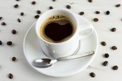 Vista dianteira de um copo delicioso e saboroso do café recentemente feito com feijões de café imagens de stock