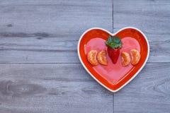 Vista dianteira de um prato coração-dado forma com morangos e tangerina para dentro, em um assoalho cinzento neutro fotos de stock