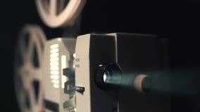 Vista dianteira de um projetor de filme super antigo antiquado de 8mm, projetando um feixe de luz em uma sala escura ao lado da filme