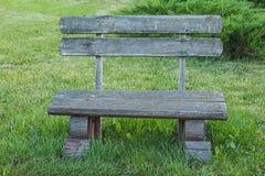 Vista dianteira do banco de madeira feito a mão velho que está no gramado perto do ju Fotografia de Stock Royalty Free