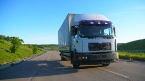 Vista dianteira do caminhão com o reboque da carga que apressa-se na estrada e que transporta bens no dia ensolarado Equitação br filme