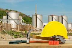 Vista dianteira do capacete de segurança amarelo, martelo, ferramentas de corte no óleo Fotografia de Stock