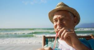Vista dianteira do cocktail bebendo do homem caucasiano superior ativo na praia 4k video estoque