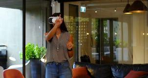 Vista dianteira do executivo fêmea caucasiano novo que usa auriculares da realidade virtual no escritório moderno 4k filme
