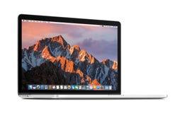 Vista dianteira do girado em uma leve retina 15 de Apple MacBook Pro do ângulo com a serra do macOS na exposição Imagens de Stock