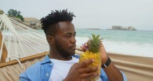 Vista dianteira do suco de abacaxi bebendo do homem afro-americano na praia 4k filme