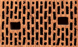 Vista dianteira do tijolo vermelho com buracos negros Imagens de Stock