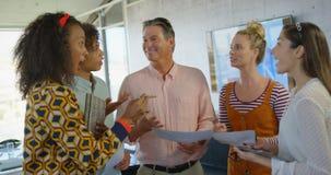 Vista dianteira dos executivos empresariais da misturado-raça que interagem junto no escritório moderno 4k filme