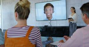 Vista dianteira dos executivos fêmeas caucasianos novos que dão a apresentação durante a videoconferência 4k filme