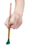 Vista diretta della mano con il pennello verde di arte Immagine Stock