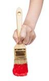 Vista diretta della mano del pittore con il pennello rosso Immagini Stock Libere da Diritti