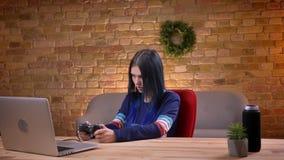 Vista diritta del primo piano di giovane video blogger femminile adolescente che gioca i video giochi facendo uso della console s stock footage
