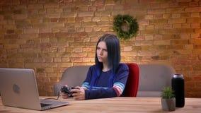 Vista diritta del primo piano di giovane video blogger femminile attraente che gioca i video giochi facendo uso della console sul archivi video