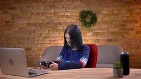 Vista diritta del primo piano di giovane video blogger femminile caucasico che gioca i video giochi facendo uso della console sul video d archivio