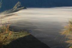 Vista distante de un pueblo brumoso en el acantilado Fotografía de archivo libre de regalías