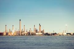 Vista distante de una refinería de la línea de la playa fotografía de archivo