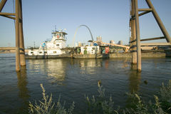 Vista diurna del barco del tirón que empuja el río Misisipi de la gabarra hacia abajo delante del arco de la entrada y el horizon Fotografía de archivo libre de regalías