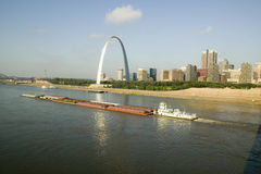 Vista diurna del barco del tirón que empuja el río Misisipi de la gabarra hacia abajo delante del arco de la entrada y el horizon Imágenes de archivo libres de regalías