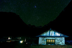 Vista do alojamento da montanha no céu estrelado da noite no fundo Imagens de Stock
