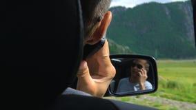 A vista do assento traseiro de um carro em um homem novo refletiu em um espelho retrovisor vídeos de arquivo