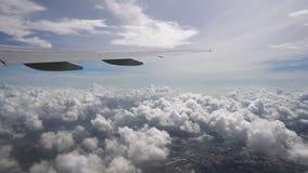 Vista do avião que voa através das nuvens sobre a cidade vídeos de arquivo