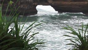 A vista do azul acena a vinda através do furo na rocha no mar, e a queda em costas vídeos de arquivo