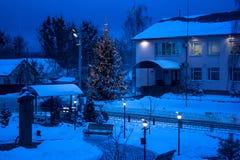 Vista do banco de encontro à árvore de Natal e da lanterna de brilho com nevar Tom azul Tiro da noite Fotos de Stock