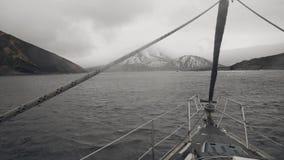 Vista do barco de navigação da curva no mar na montanha com picos nevado vídeos de arquivo
