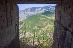 Vista do céu azul das montanhas verdes através da janela de pedra fotografia de stock