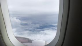 Vista do c?u azul e das nuvens atrav?s da janela dos avi?es, fim acima da janela do avi?o com asa do avi?o vídeos de arquivo