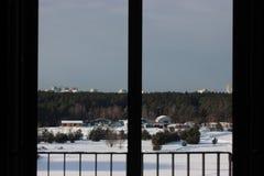 Vista do campo e a floresta do inverno, prédios na distância e guindastes de construção, neve limpa em um dia ensolarado imagens de stock royalty free