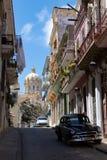 Vista do carro do oldtimer com balcões coloniais e o palácio antigo do ditador Batista agora o museu da revolução imagens de stock