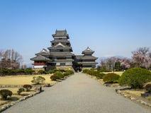 Vista do castelo bonito do corvo de Matsumoto através da estrada da entrada com fundo da montanha da neve e do céu azul durante a Fotos de Stock