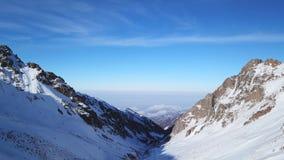 Vista do desfiladeiro nevado nas montanhas às nuvens e à poluição atmosférica da cidade foto de stock royalty free