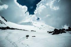 Vista do Elbrus ocidental em nuvens grossas perto do local de uma queda dum helicóptero foto de stock