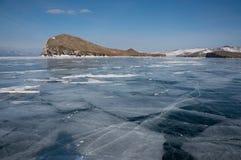 a vista do gelo cobriu a superfície da água de formações do lago e de rocha no fundo, Rússia, imagem de stock