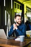 Vista do homem farpado lateral em uma camisa usando um portátil que senta-se em uma tabela em um café na xícara de café da tabela Fotos de Stock Royalty Free