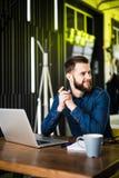 Vista do homem farpado lateral em uma camisa usando um portátil que senta-se em uma tabela em um café na xícara de café da tabela Imagem de Stock