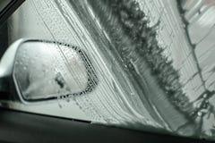 Vista do interior do carro a tomar partido espelho e janela que são i lavado imagens de stock royalty free