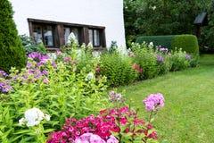 Vista do jardim bem conservado com um gramado verde, as flores e as árvores perto da casa fotografia de stock