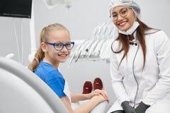 Vista do lado da menina feliz que senta-se no escritório do dentista imagens de stock royalty free