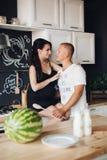 Vista do lado de pares bonitos que beija ao cozinhar na cozinha fotografia de stock royalty free