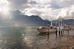 Vista do lago Como em um dia nebuloso com barco a motor e do porto em Bellagio Imagens de Stock